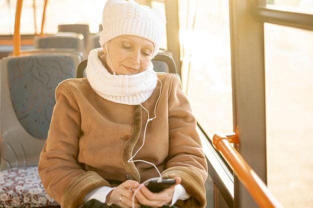 Mulher mais velha de ângulo alto em ouvir música de ônibus Foto gratuita