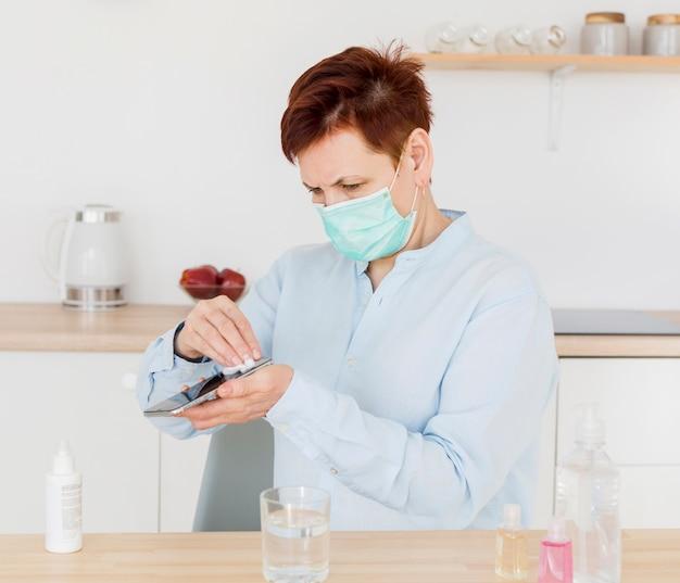 Mulher mais velha desinfetar o telefone enquanto usava máscara médica Foto gratuita
