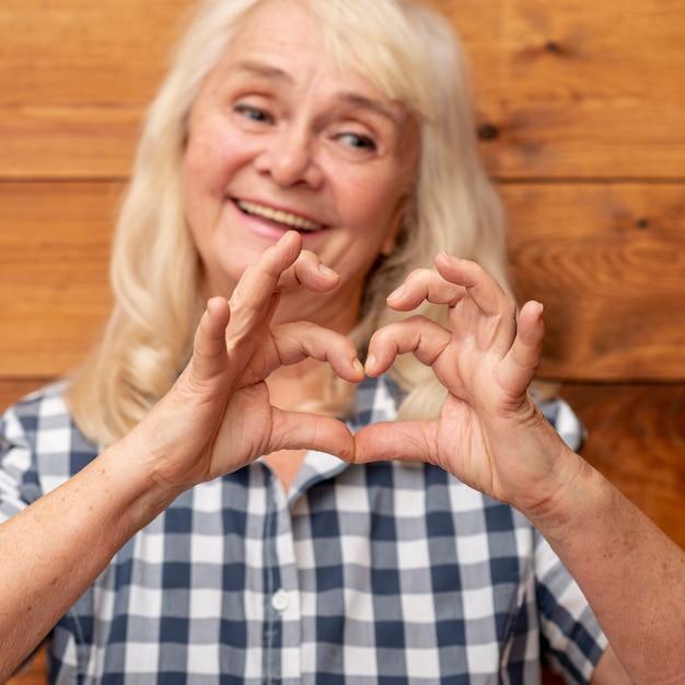 Mulher mais velha, mostrando a forma do coração de mão Foto gratuita