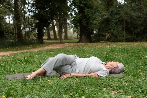Mulher mais velha praticando yoga no exterior Foto Premium