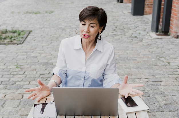 Mulher mais velha, sentado ao ar livre com o laptop Foto gratuita