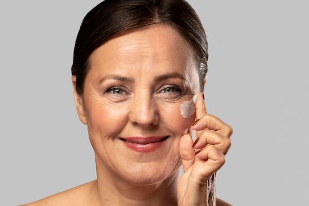 Mulher mais velha sorridente usando hidratante no rosto Foto gratuita