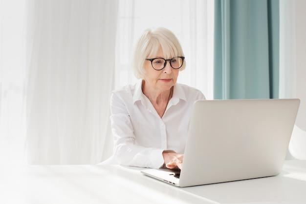 Mulher mais velha, trabalhando em um laptop em seu escritório Foto gratuita