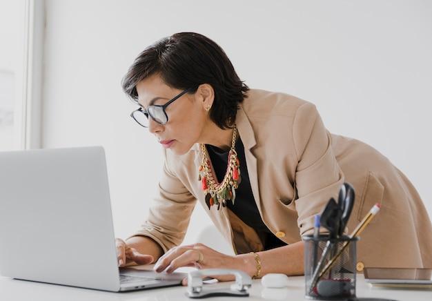 Mulher mais velha trabalhando no laptop Foto gratuita