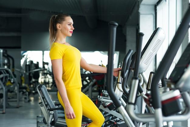 Mulher malhando na máquina elíptica no ginásio Foto Premium