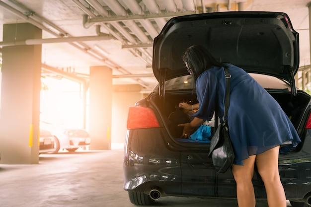 Mulher, mantenha, saco, em, tronco carro, em, lote estacionamento Foto Premium