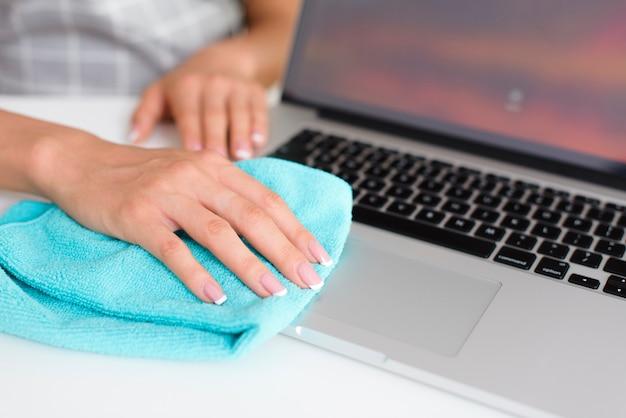 Mulher, mão, limpeza, laptop, casa Foto gratuita