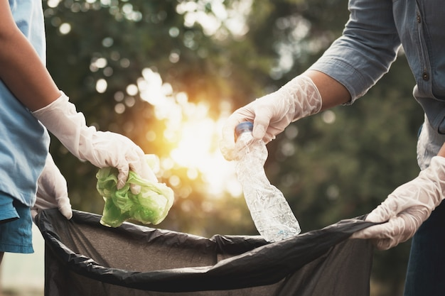 Mulher mão pegando lixo plástico para limpeza no parque Foto Premium