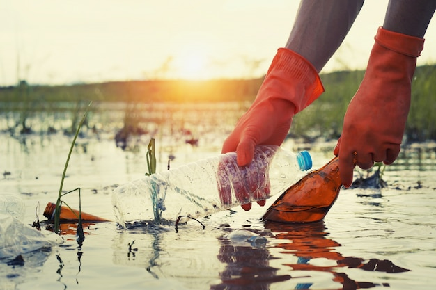 Mulher mão pegando lixo plástico para limpeza no rio com pôr do sol Foto Premium