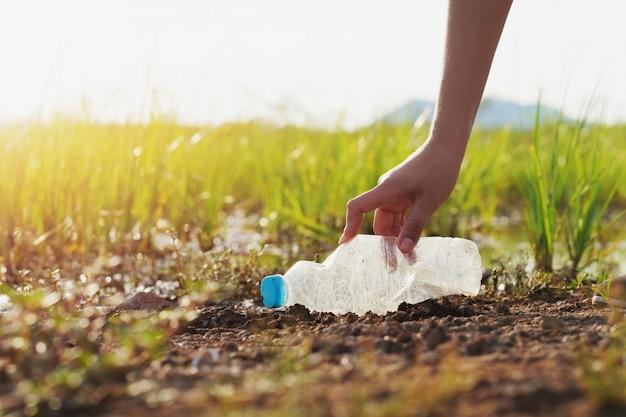 Mulher mão pegando lixo plástico para limpeza no rio Foto Premium