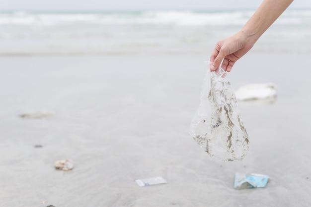 Mulher mão, pegando, sacola plástica, limpeza, praia Foto Premium