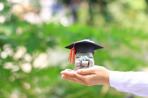 Mulher mão, segurando, dinheiro moedas, em, garrafa copo, com, graduados, chapéu, ligado, natural, experiência verde Foto Premium