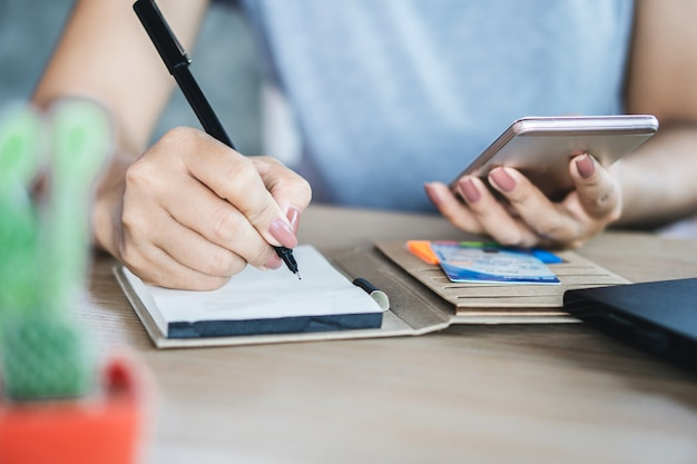 Mulher mão segurando o telefone inteligente cálculo de dívida Foto Premium
