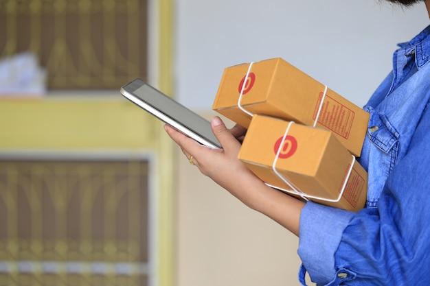Mulher mão segurando o telefone inteligente e parcela de rastreamento on-line para atualizar o status com holograma Foto Premium