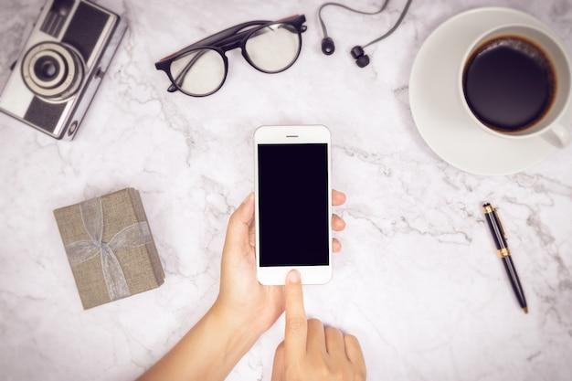 Mulher mão uso simulado acima da tela preta em branco do telefone móvel com o dedo na tela de toque Foto Premium