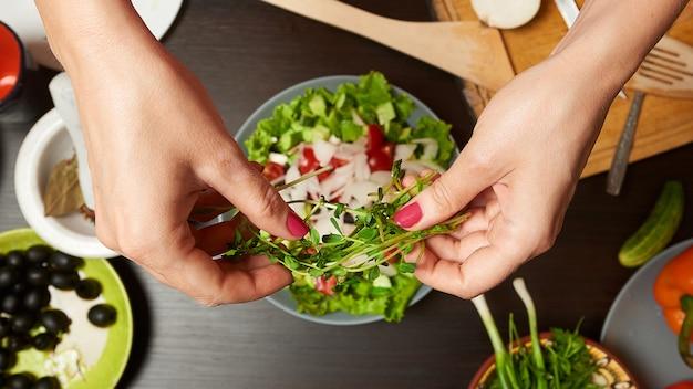 Mulher mãos adicionando microgreens em salada saudável Foto Premium