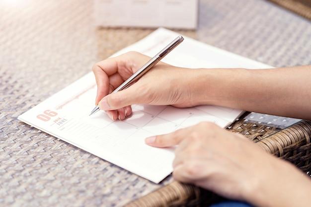 Mulher, mãos, escrita, plano, ligado, caderno, planificação, agenda, e, cronograma, usando, calendário Foto Premium