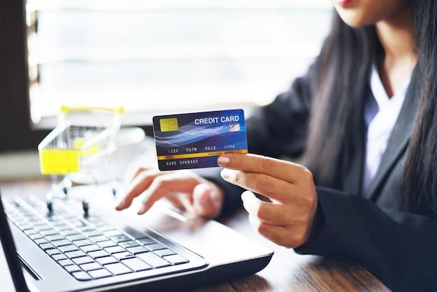 Mulher, mãos, segurando, cartão crédito, e, usando computador portátil, para, shopping online, em, um, escritório, tabela, carrinho de compras, /, pessoas trabalhando, pagar tecnologia, dinheiro, carteira, pagamento online Foto Premium