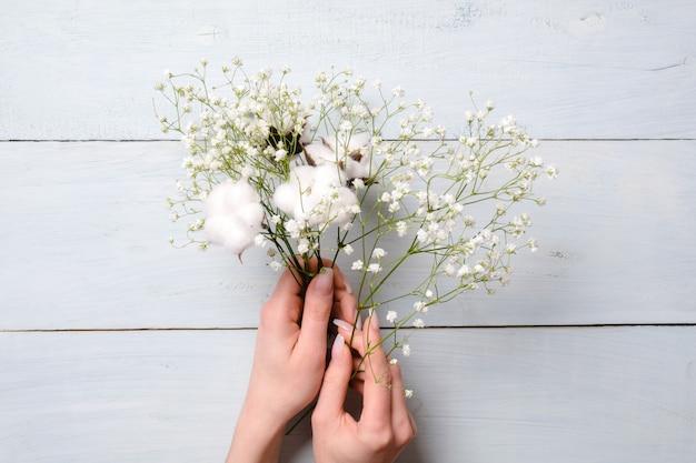Mulher mãos segurando flores de monte sobre fundo azul de madeira. Foto Premium