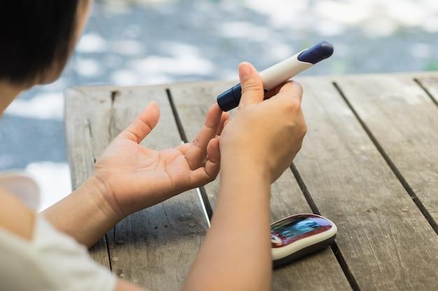 Mulher mãos usando lanceta no dedo para verificar o nível de açúcar no sangue diabetes por medidor de glicose Foto Premium