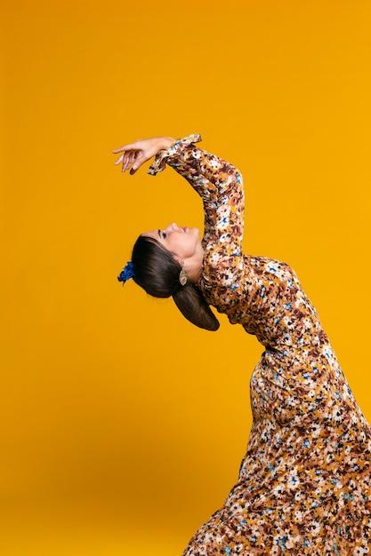 Mulher maravilhosa, curvando-se com fundo laranja Foto gratuita