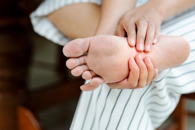 Mulher massageando seu doloroso com os pés descalços Foto Premium