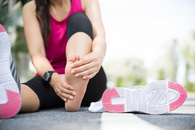 Mulher massageando seu pé doloroso. corrida esporte e conceito de lesão de exercício. Foto Premium