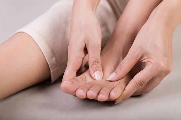 Mulher massageando seu pé doloroso. Foto Premium