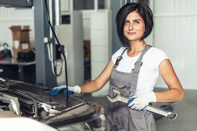 Mulher mecânica segurando a chave para consertar o carro Foto gratuita