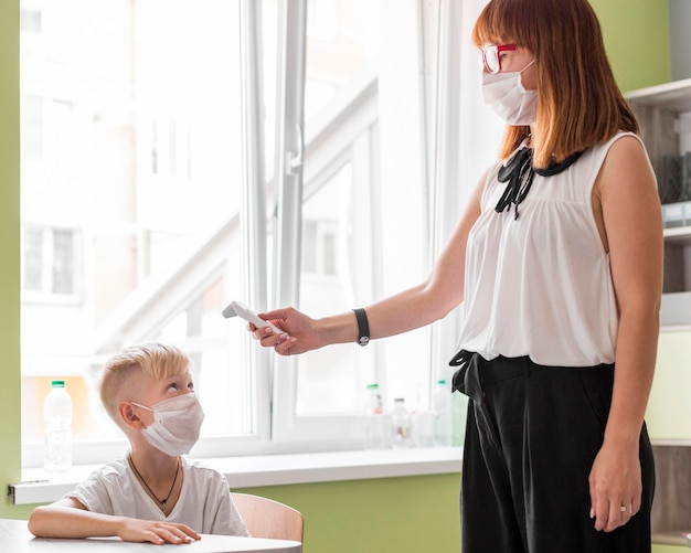 Mulher medindo a temperatura de um menino na aula Foto Premium