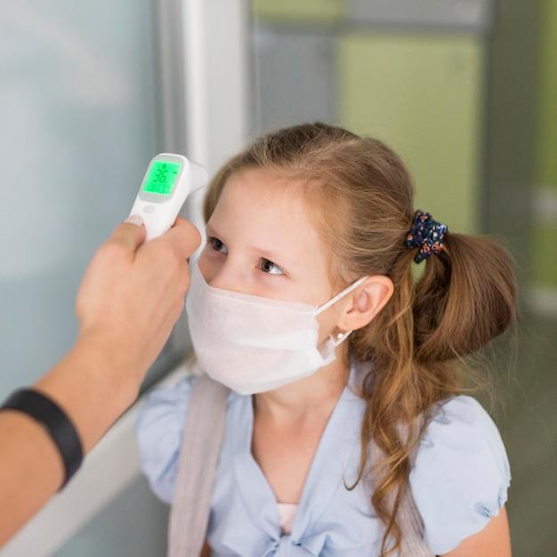 Mulher medindo a temperatura de uma menina Foto Premium