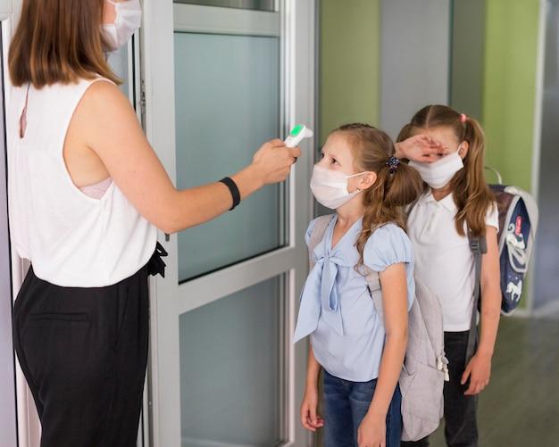 Mulher medindo a temperatura dos alunos Foto Premium