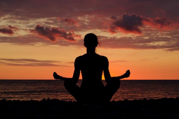 Mulher meditando na praia em posição de lótus. silhueta, pôr do sol Foto Premium