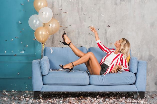 Mulher, mentindo, ligado, sofá, com, champanhe Foto gratuita