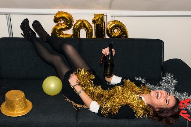 Mulher, mentindo sofá, com, garrafa champanha Foto gratuita