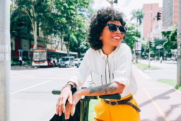 Mulher moderna em uma cidade com uma scooter elétrica Foto gratuita