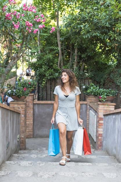 Mulher moderna posando com sacos de compras Foto gratuita