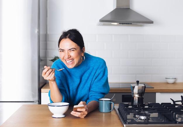 Mulher moderna tomando café da manhã na cozinha Foto gratuita