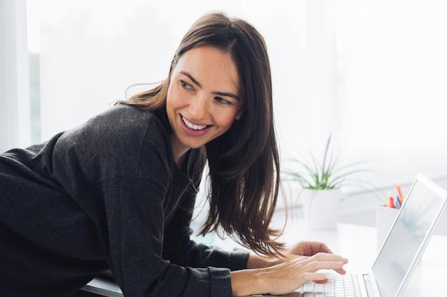Mulher moderna, usando computador portátil Foto gratuita