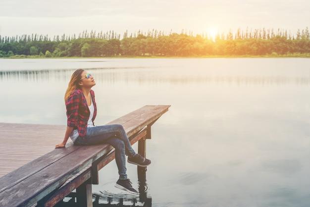 Mulher moderno bela jovem sentada no cais do lago, descontraído Foto gratuita