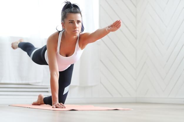 Mulher morena atraente fazendo ioga em casa. Foto gratuita