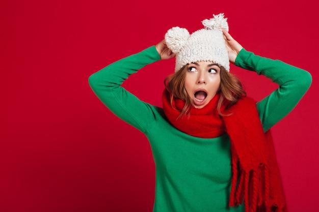 Mulher morena chocada na camisola, chapéu engraçado e cachecol Foto gratuita