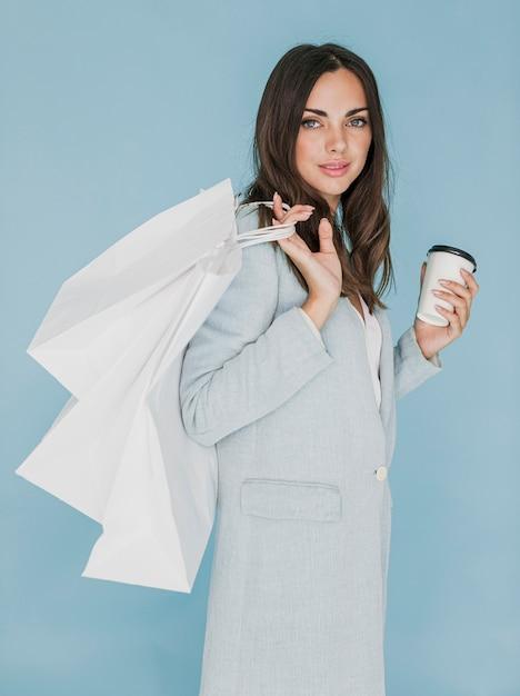 Mulher morena com café e sacolas no ombro Foto gratuita