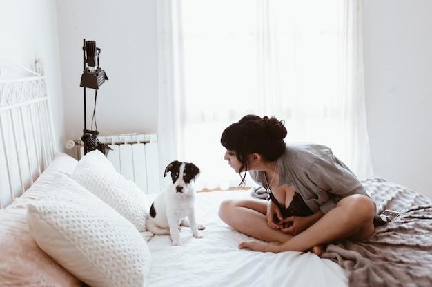 Mulher morena com seu doce cachorro no quarto Foto Premium