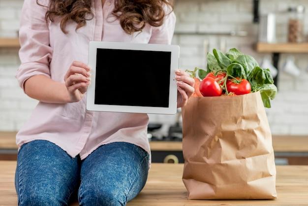 Mulher morena com um saco de papel cheio de comida saudável Foto gratuita