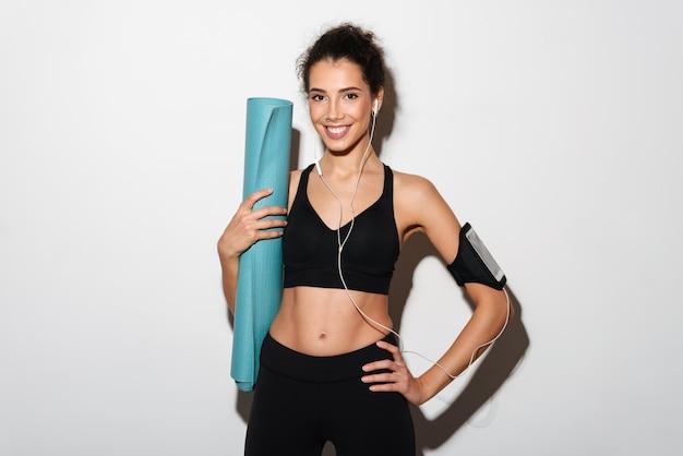 Mulher morena de esportes encaracolado sorridente segurando a esteira de fitness Foto gratuita