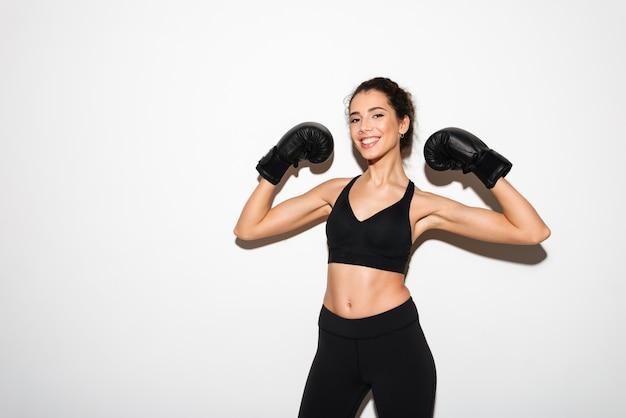 Mulher morena encaracolado fitness sorridente em luvas de boxe, mostrando o bíceps Foto gratuita