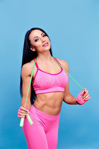 Mulher morena esportiva no sportswear rosa com pular corda Foto Premium