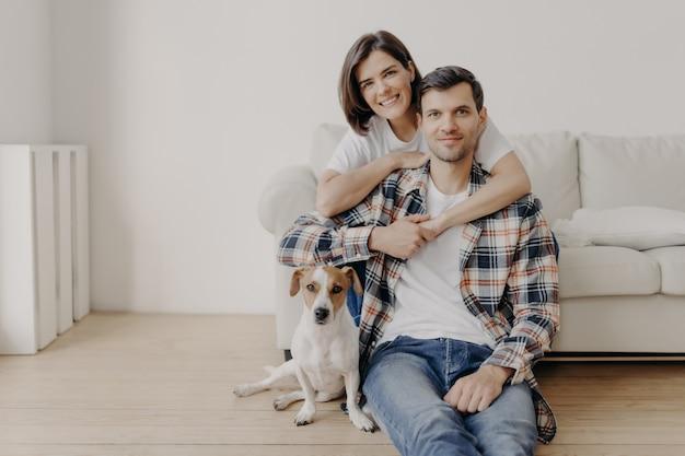 Mulher morena feliz abraça o marido com amor, estar de bom humor, sorri positivamente. marido, esposa e cachorro posam juntos na sala de nova habitação, desfrutam de conforto. casal apaixonado interior Foto Premium