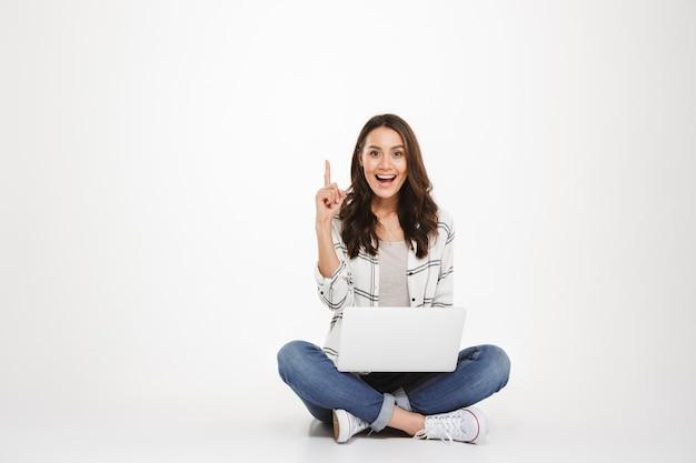 Mulher morena feliz na camisa, sentada no chão com o computador portátil, tendo a ideia e olhando para a câmera sobre cinza Foto gratuita